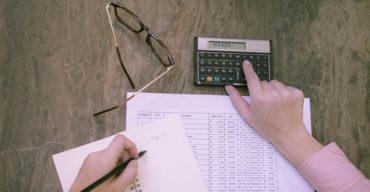 Mão calculando os impostos ISS ou ICMS