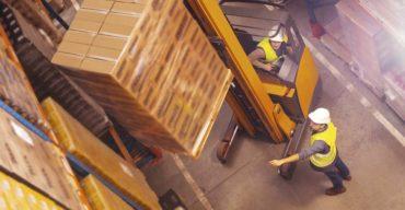 Profissionais elevam cargas durante a armazenagem de mercadorias