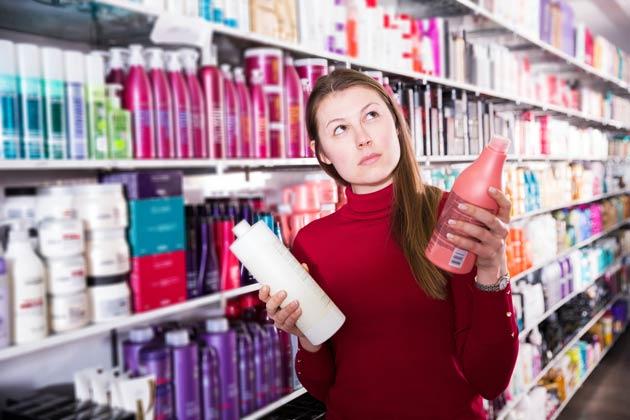 mulher em dúvida ao escolher cosméticos