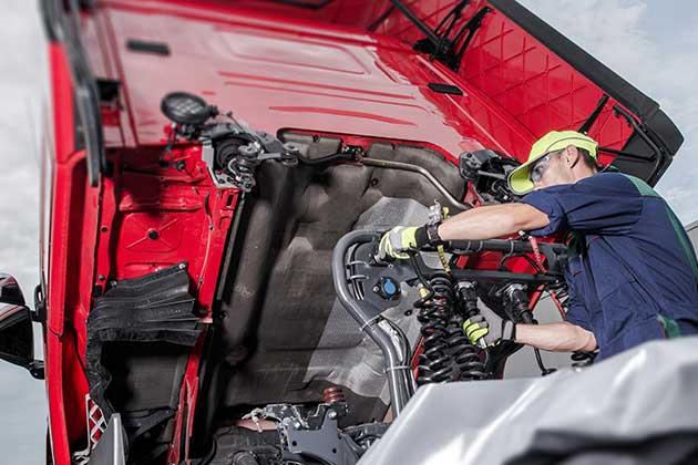 homem consertando o motor fazendo a gestão de frotas de caminhões
