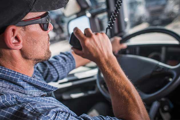 motorista com rádio fazendo a gestão de frotas de caminhões