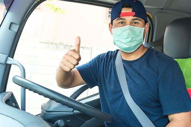 caminhoneiro de máscara ao volante faz sinal de positivo à instalação de radares de velocidade nas rodovias