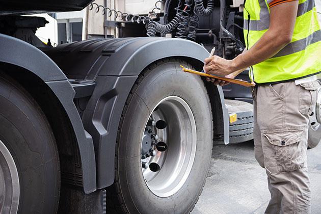 mecânico olhando as peças do veículo exemplificando os cuidados que todo caminhoneiro deve ter